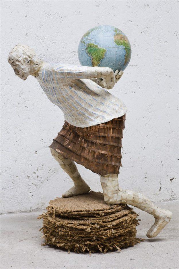In dit beeld draagt een vrouw een wereldbol op haar rug als een symbool voor de zorg die we moeten hebben voor de planeet aarde. Een oproep om hiermee zorgvuldig om te gaan.